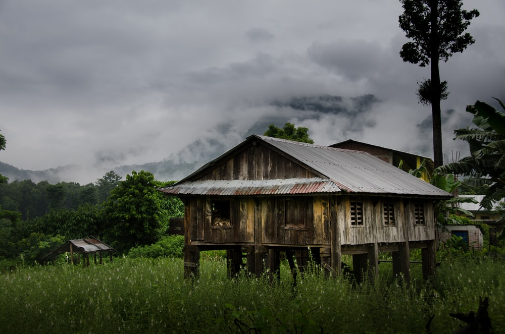 brown wooden house on green grass field under cloudy sky