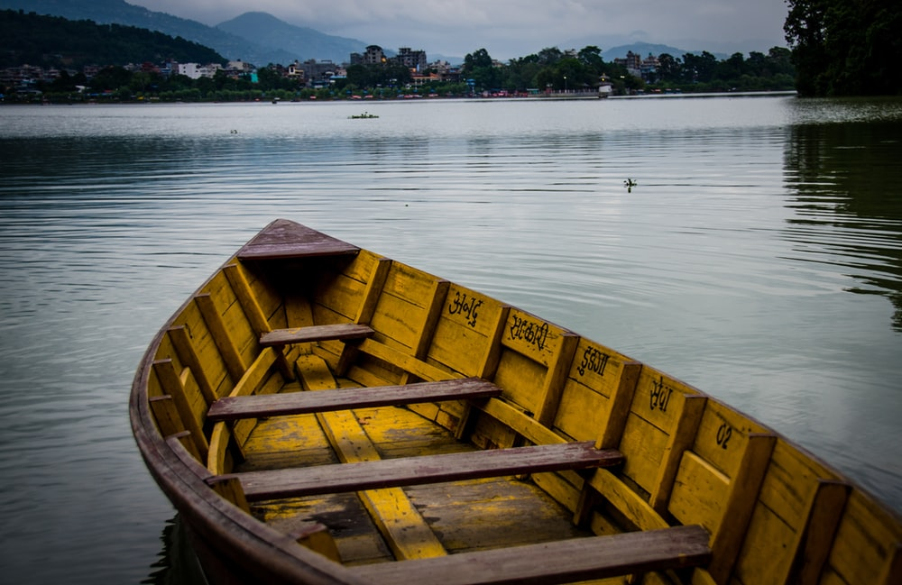 yellow and brown wooden boat on lake during golden hour