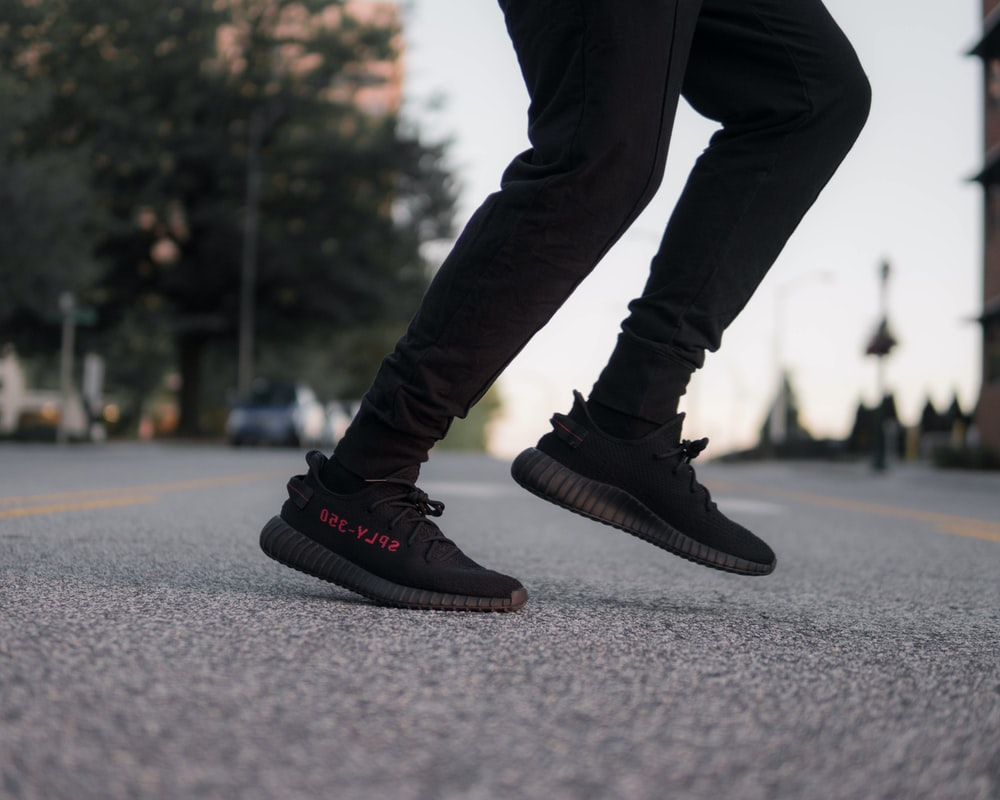 person wearing black-and-red adidas Yeezy Boost 350 v2 sneakers