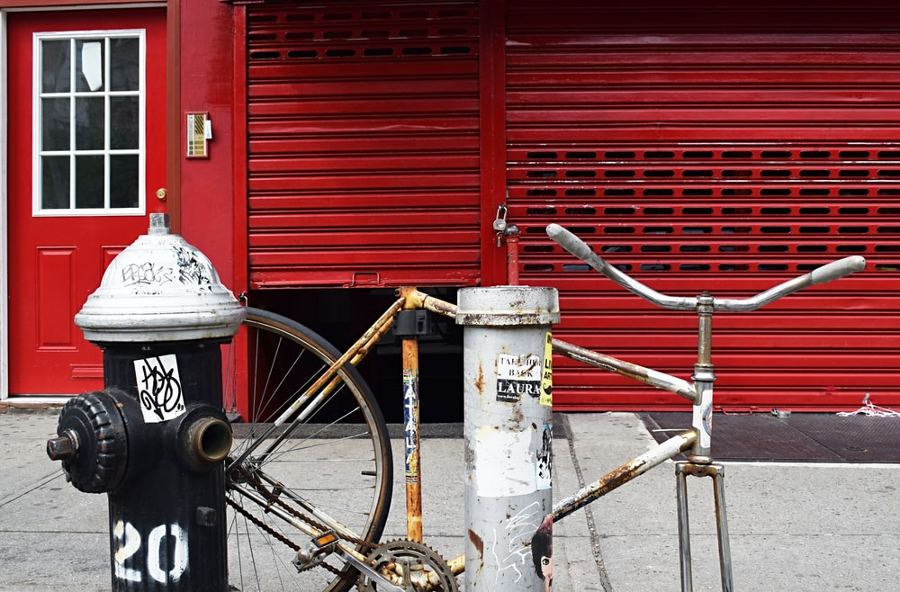 red bicycle parked beside gray metal tank