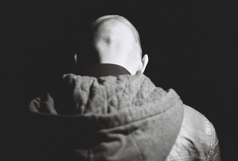 grayscale photography of person wearing jacket