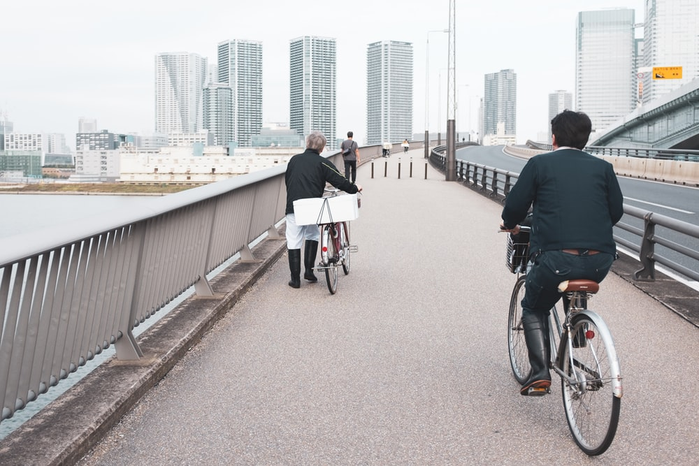 two person riding bicycle near ocean