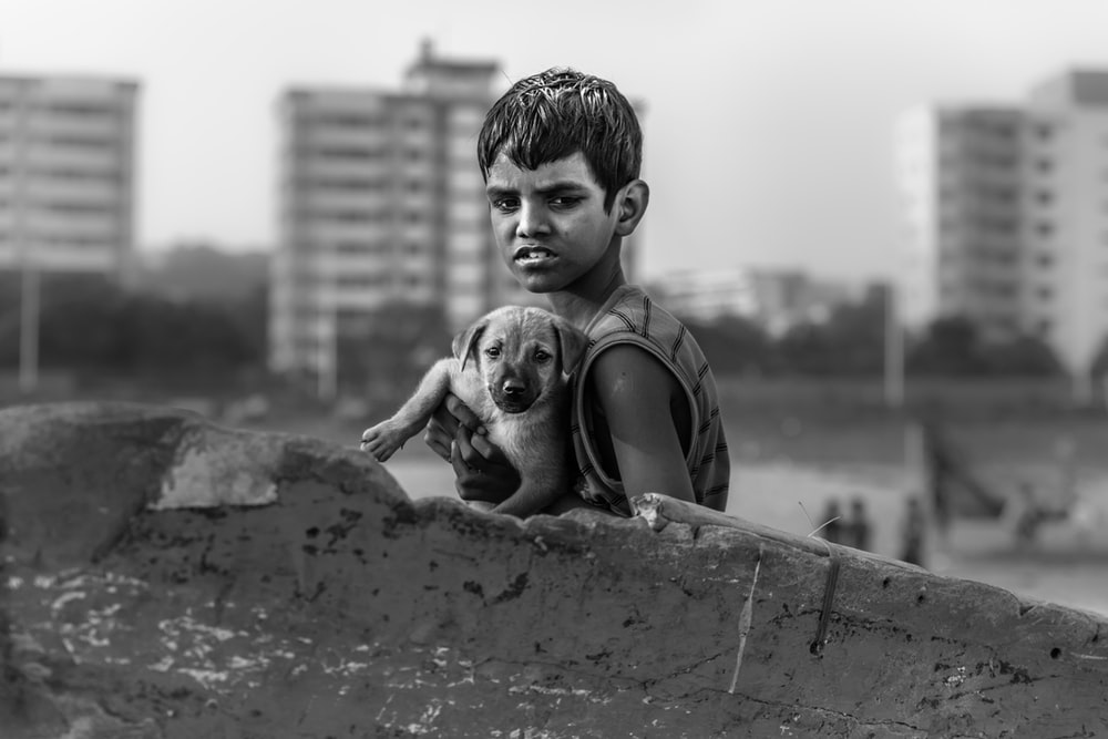 boy on sleeveless top holding puppy black and white photography