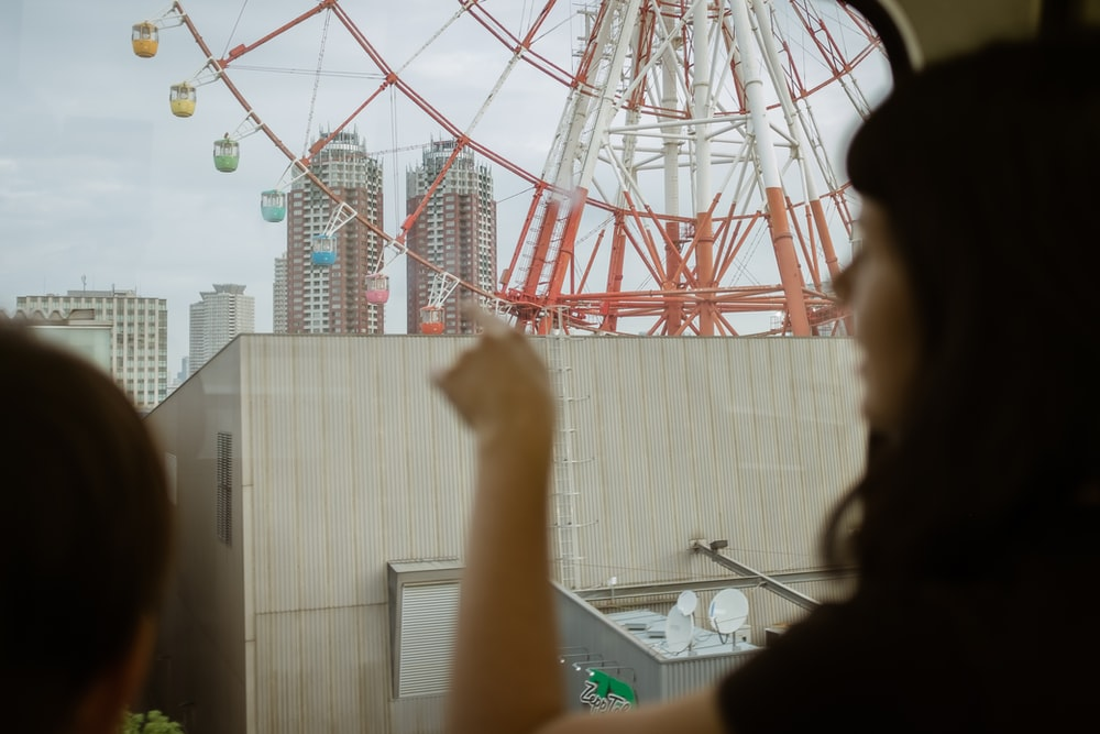 selective focus photography of man in front of ferris wheel