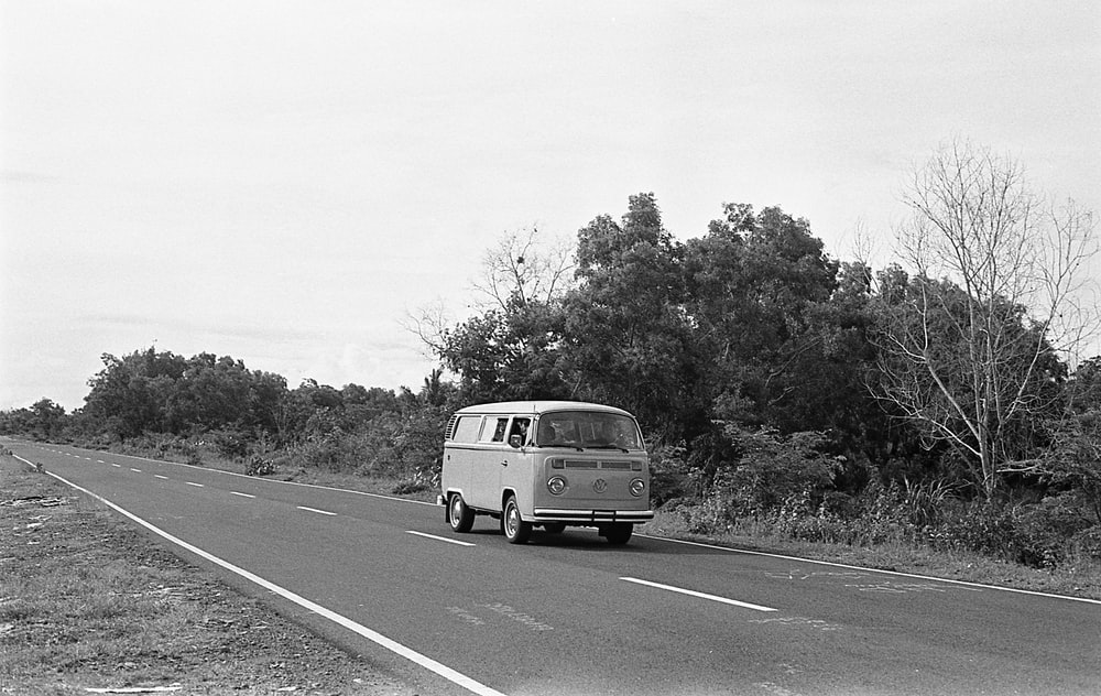 grayscale photography of Volkswagen T2 on the road near trees
