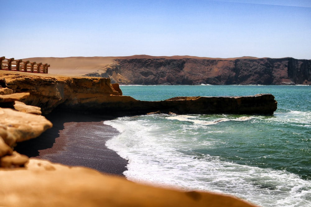 wide angle photography of brown cliff near body of water