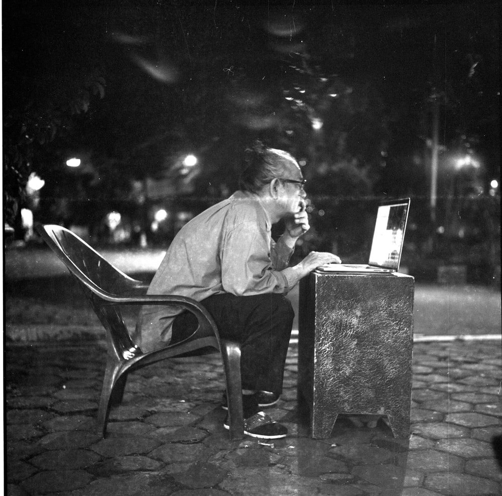 man sitting on chair infront of table while looking at laptop