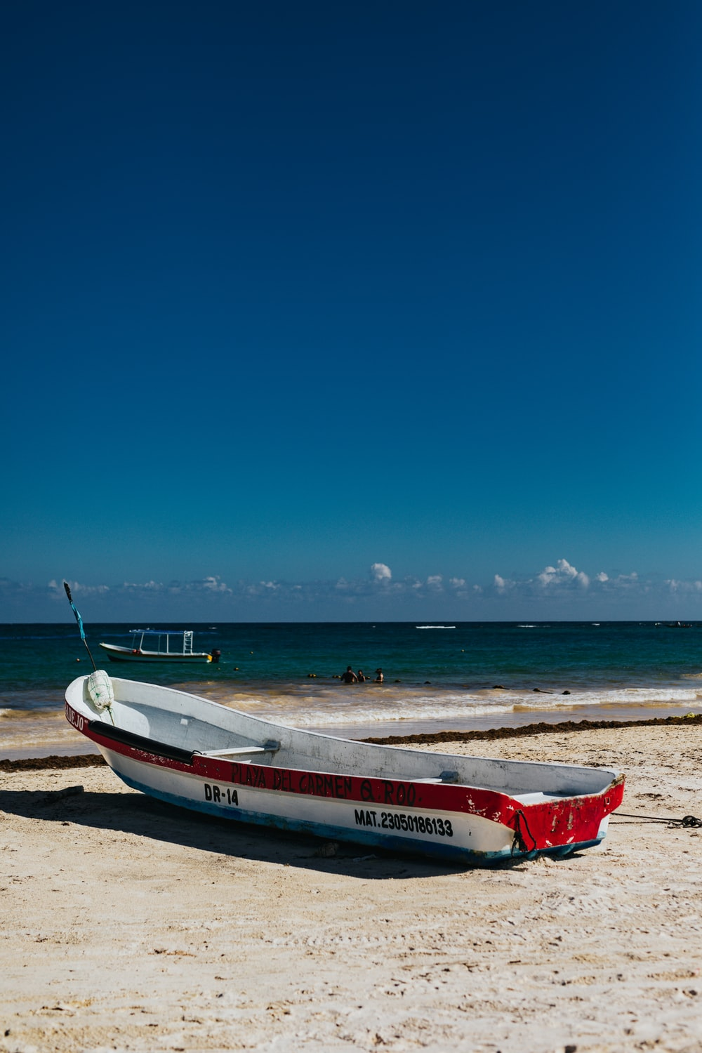 white and red row boat on shoe under blue sky during daytime