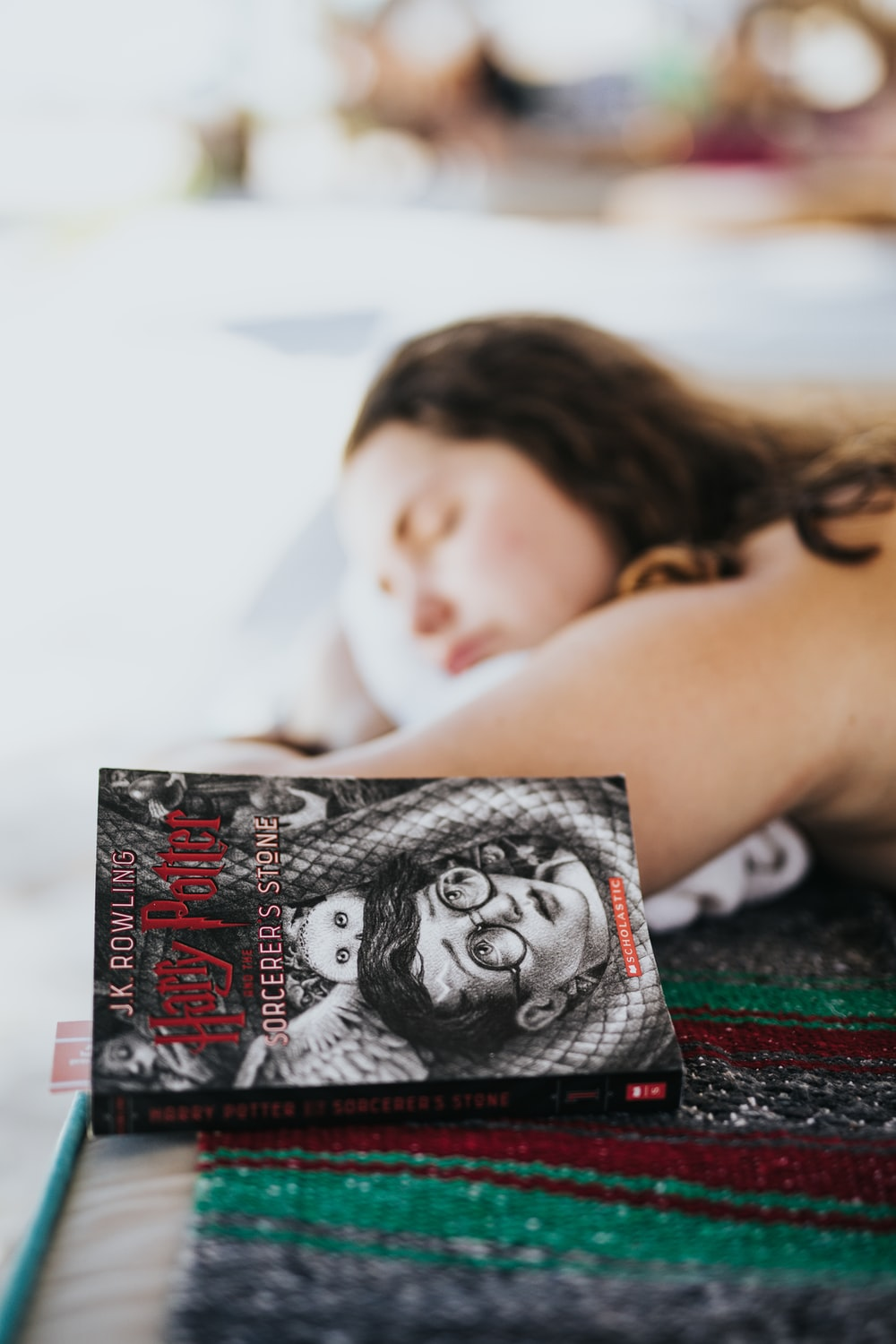 woman lying in prone position beside closed Harry Potter book