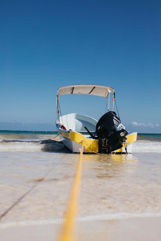 white speedboat on shore at daytime