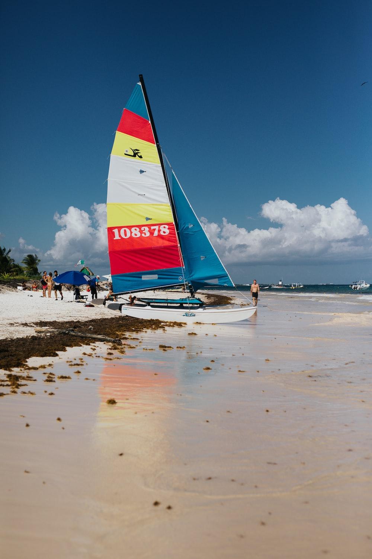 white sailboat on shore at daytime