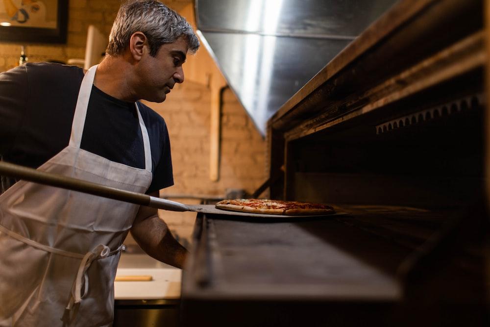 man baking pizza
