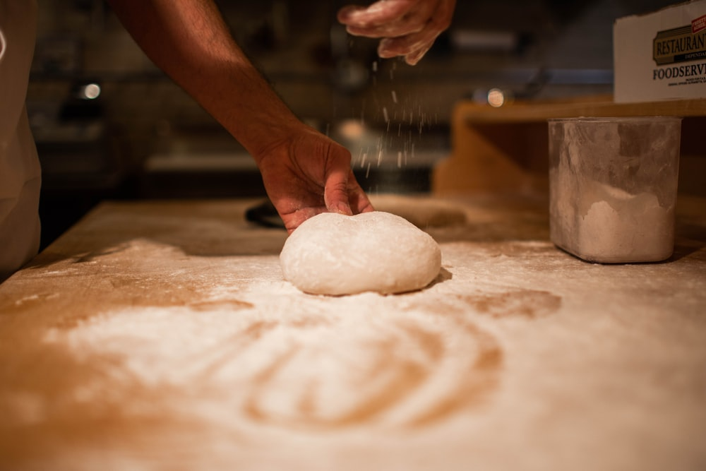 person holding bread dough on table