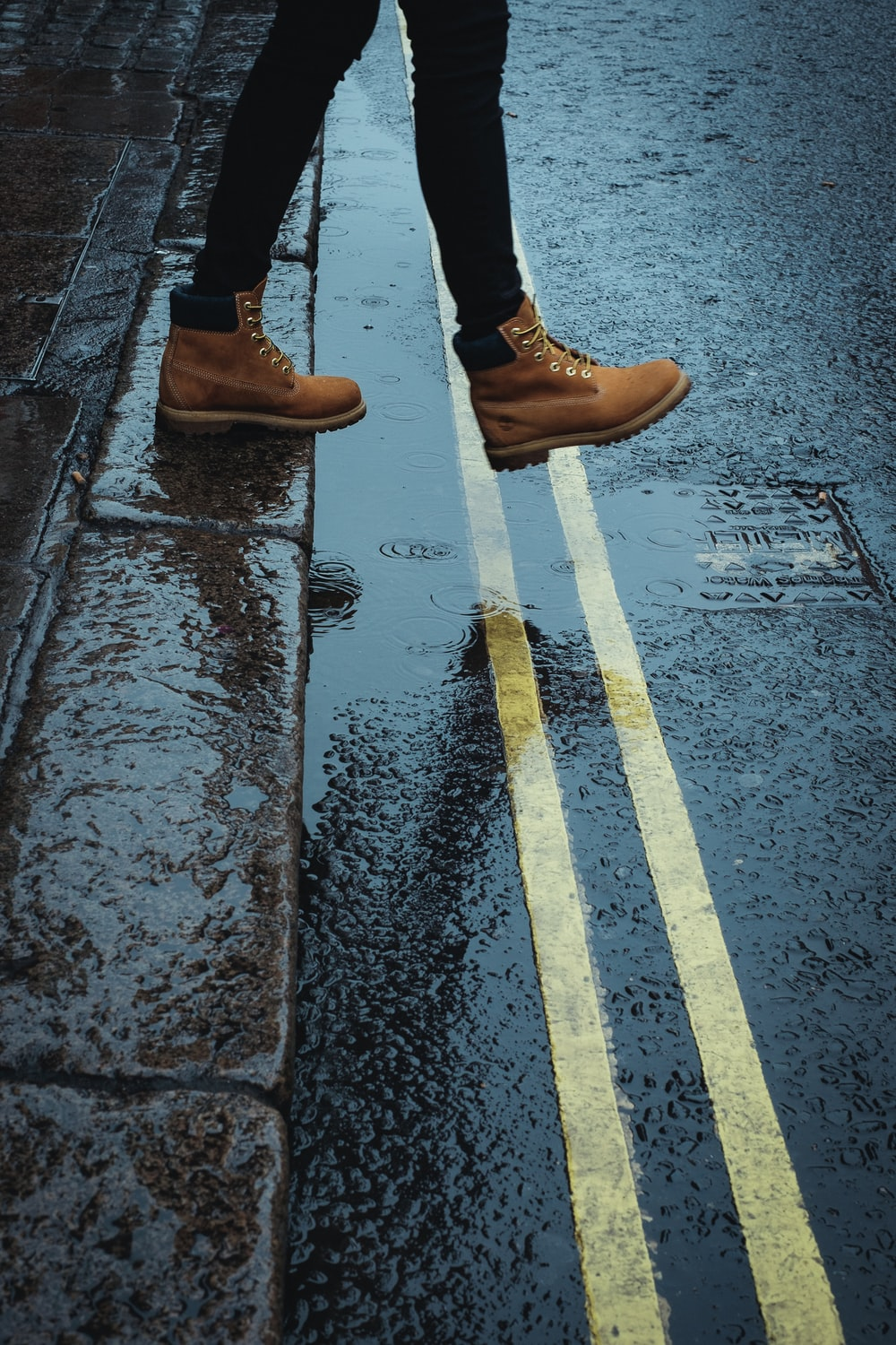 person wearing brown boots walking on a wet road