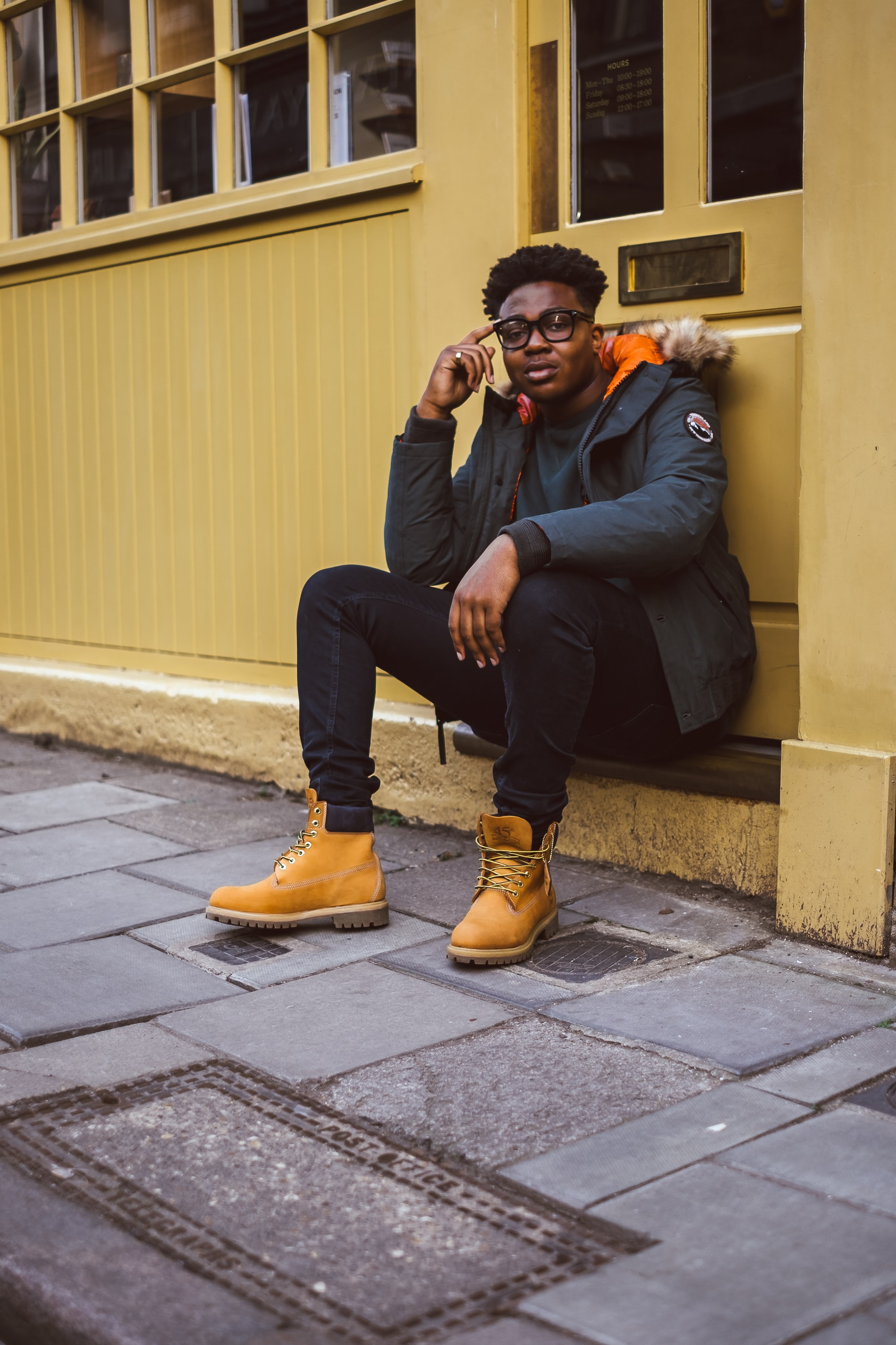 A man sitting wearing Timberland yellow boots