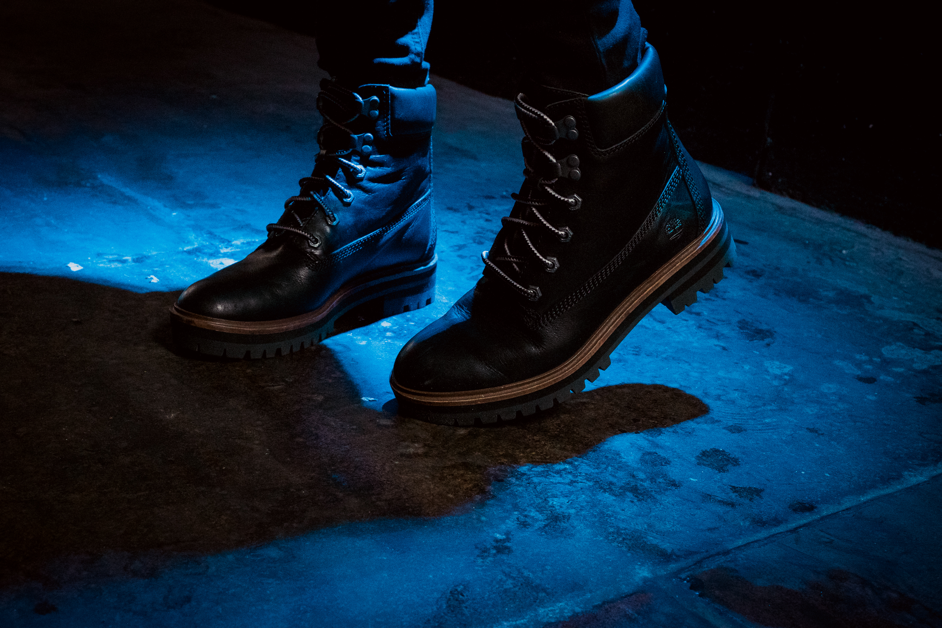 Person Wearing Black Work Boots Standing On Concrete Surface