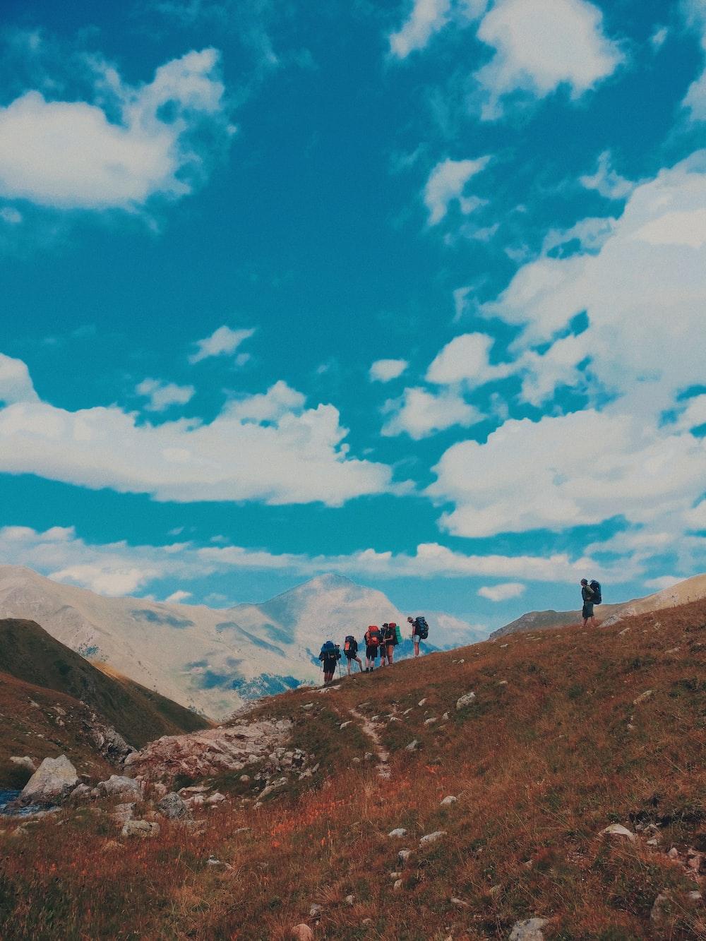 group of people standing on mountain range