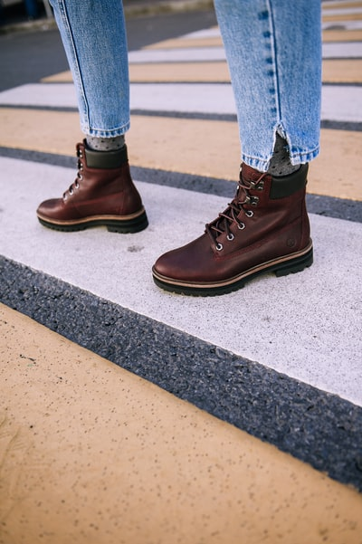 person wearing pair of brown leather boots