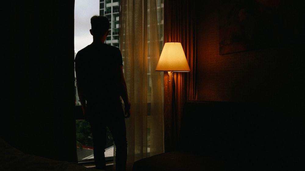man standing beside floor lamp