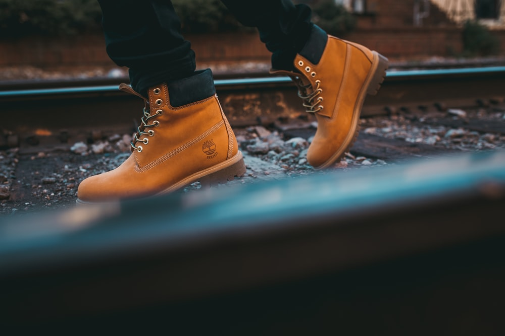 A person walks on a railway track wearing a pair of yellow Timberland boots