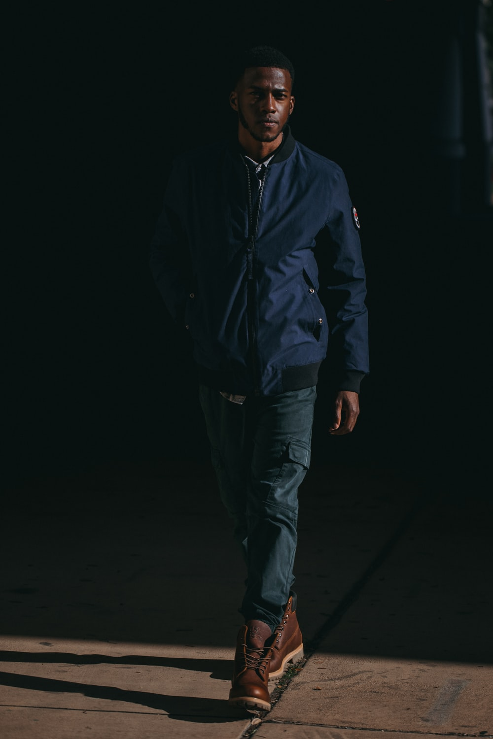 man wearing blue jacket and brown leather boots