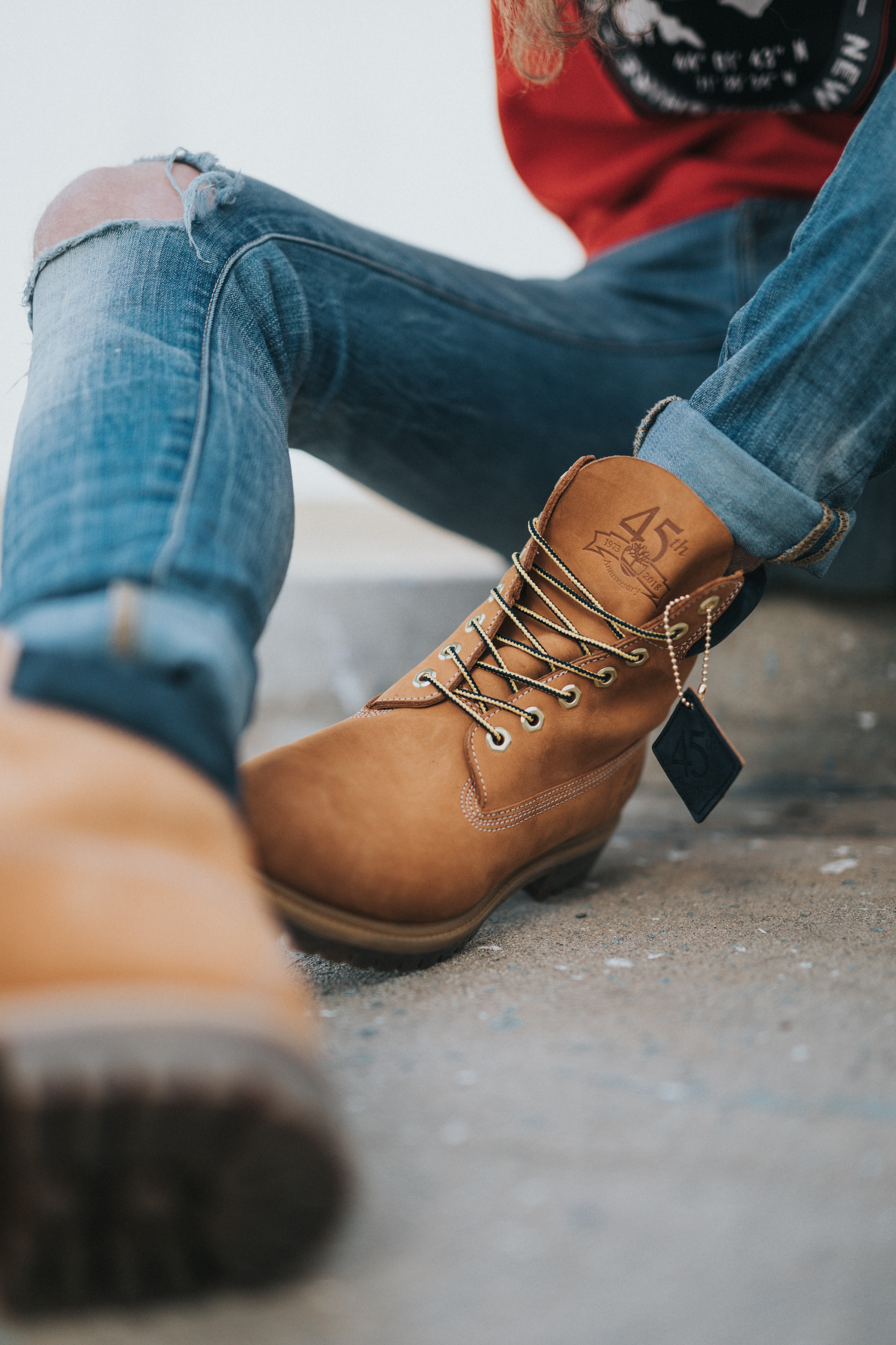 A man sits wearing his Timberland boots