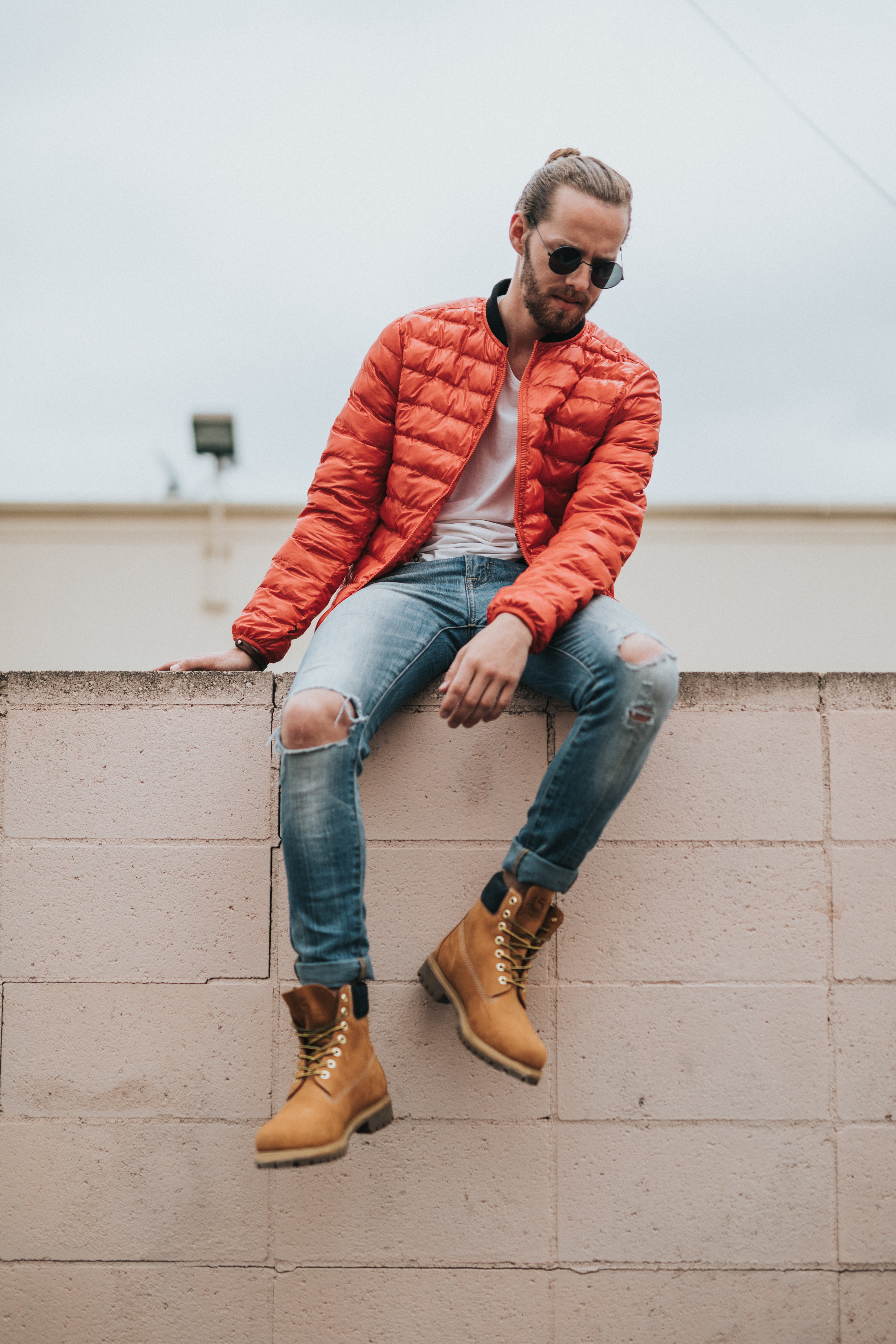 A man poses on a wall wearing a red jacket, jeans, and Timberland boots