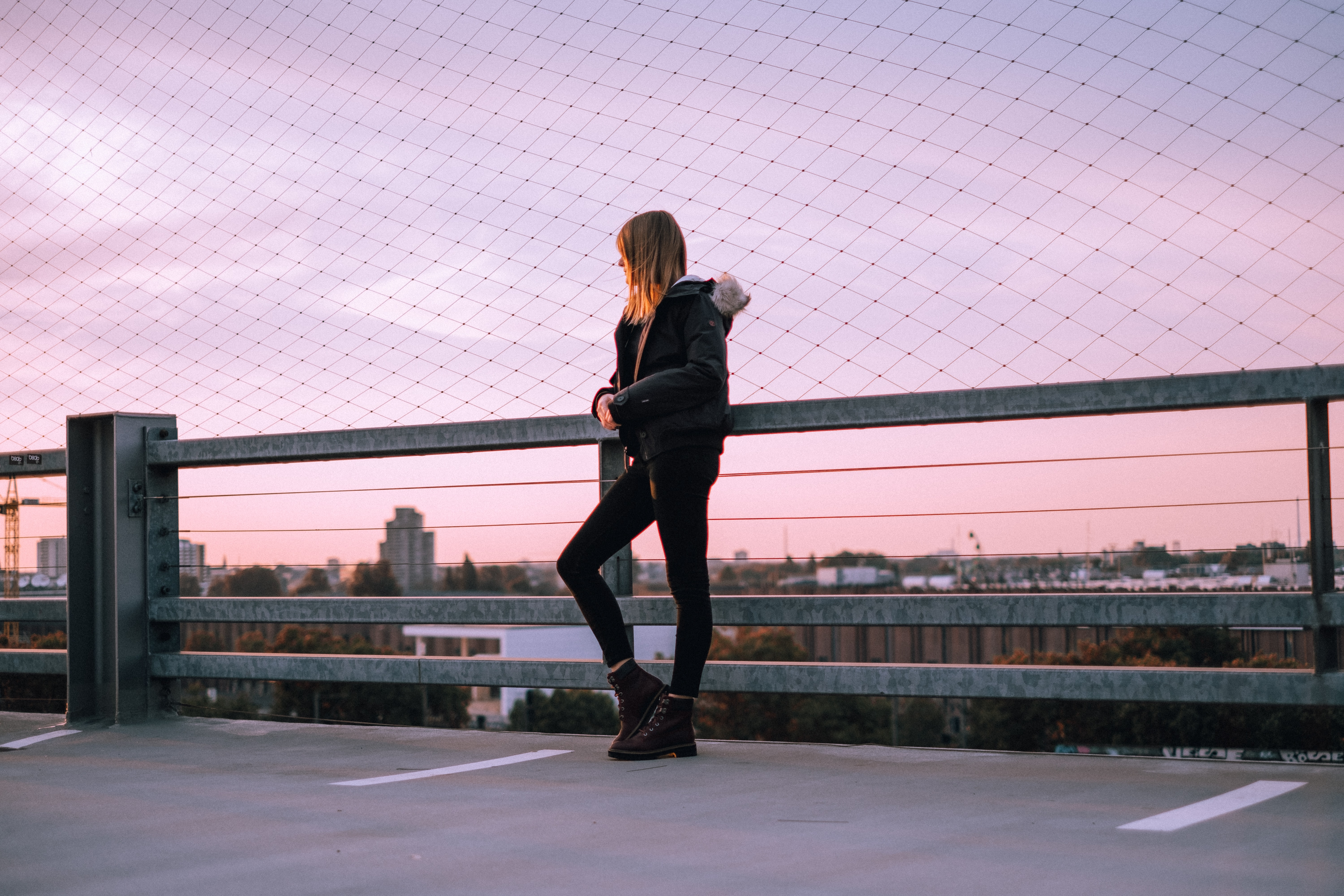 A woman poses wearing a Timberland jacket and boots in front of a purple sky