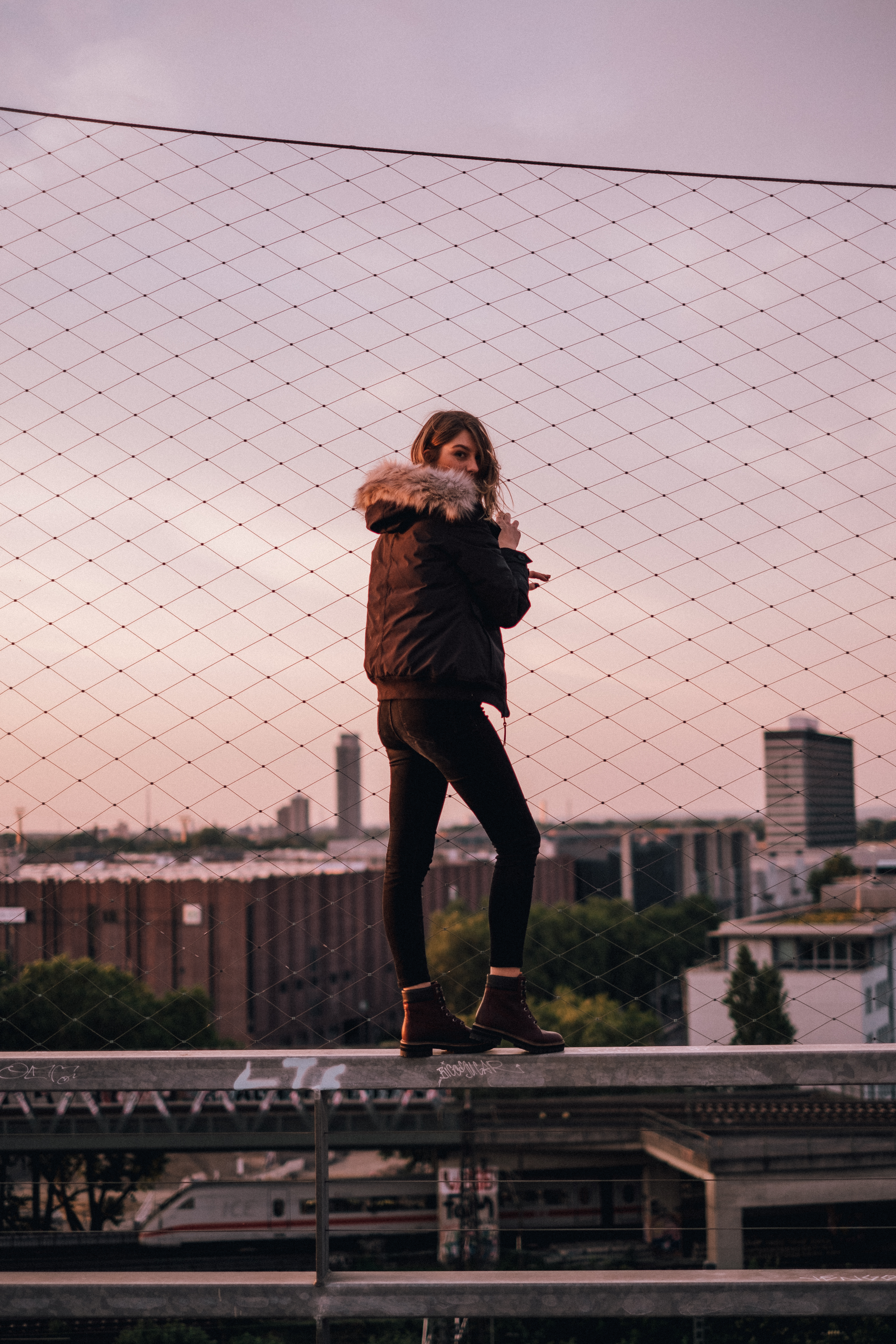 A Woman Poses In Front Of Rooftops Wearing A Timberland Parka And Timberland Boots