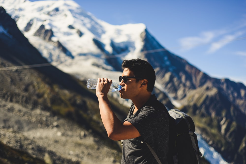man drinking water at top of mountain