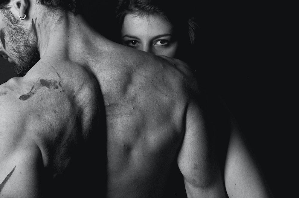 woman standing behind topless man