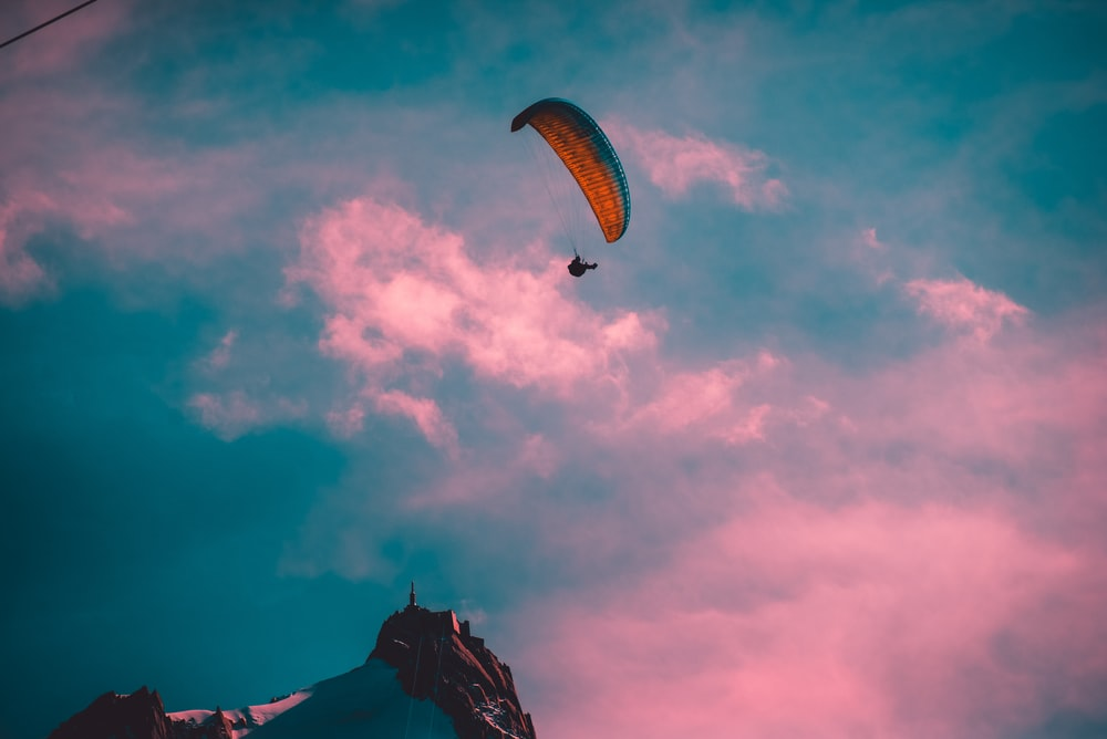 person with parachute by mountain