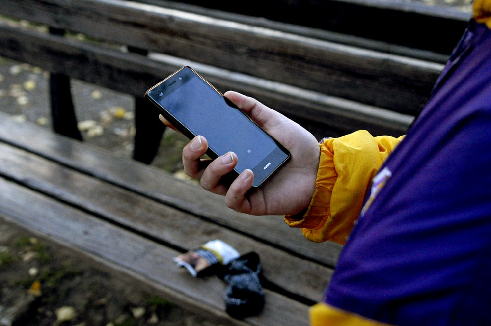 person standing and holding black smartphone