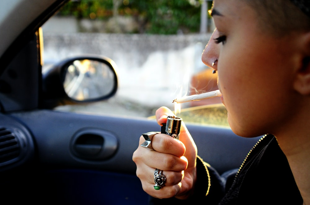 woman lighted cigarette stick inside car
