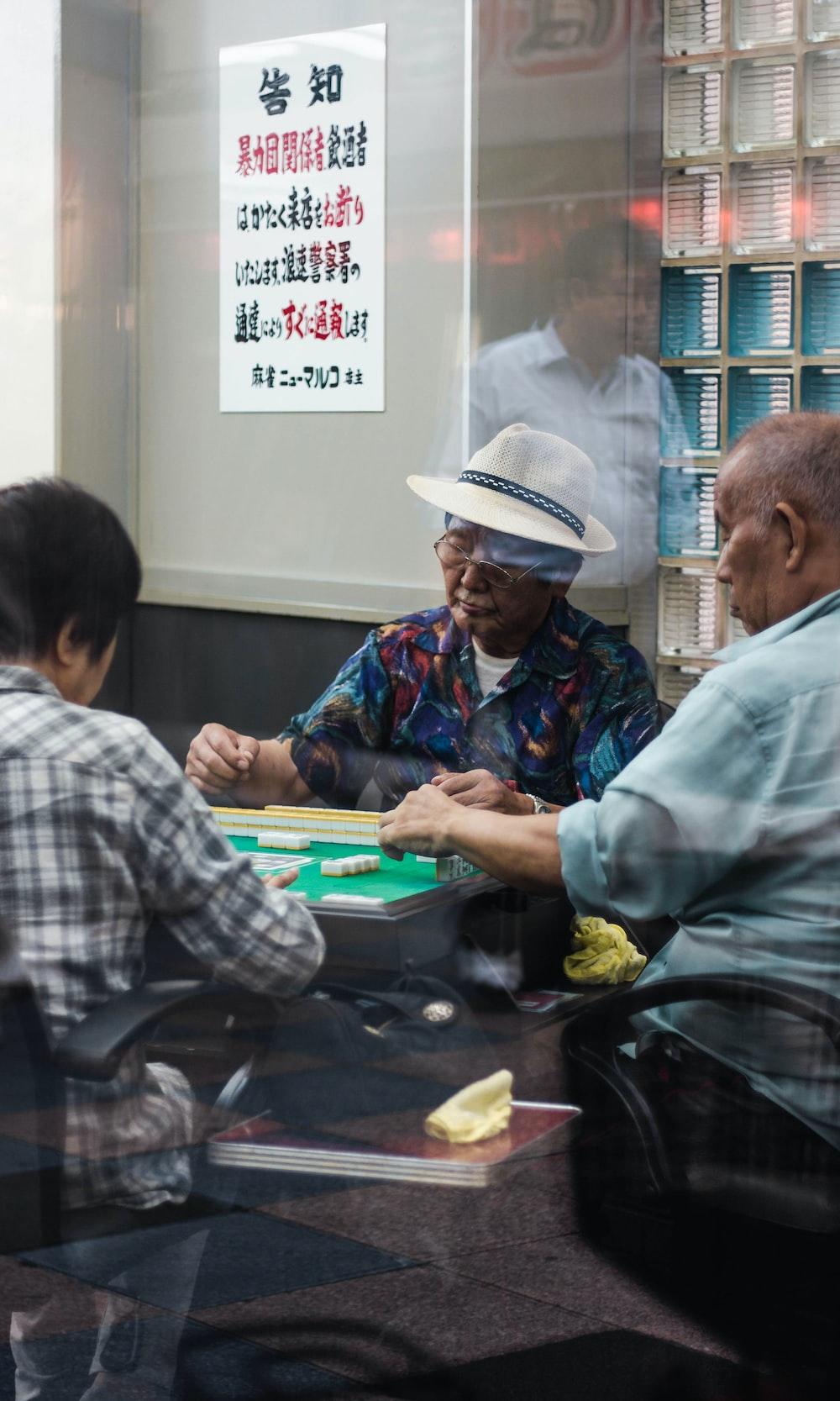 three man sitting playing mahjong inside room