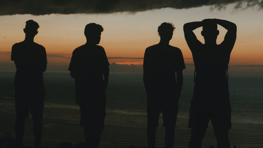 silhouette of four men at the beach