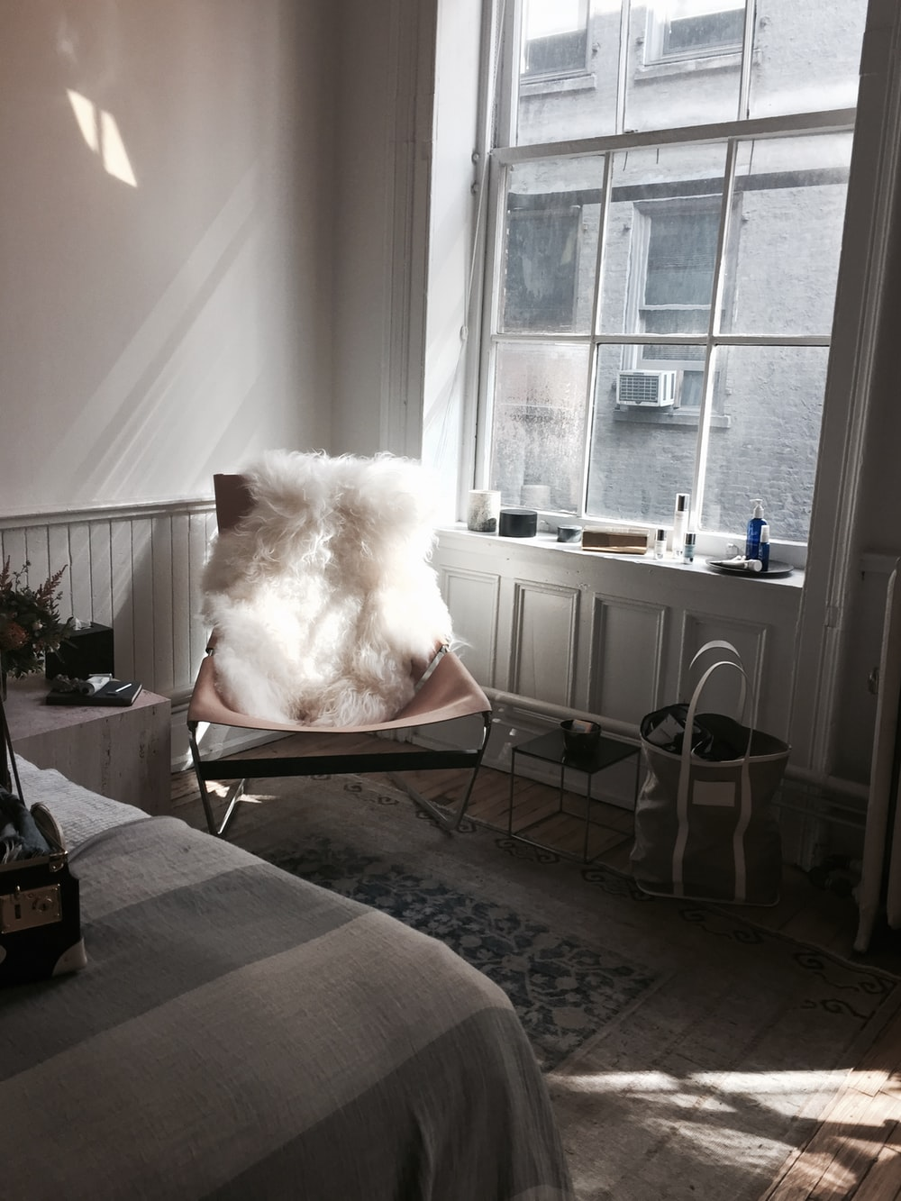 white fur chair cover on brown chair beside glass window