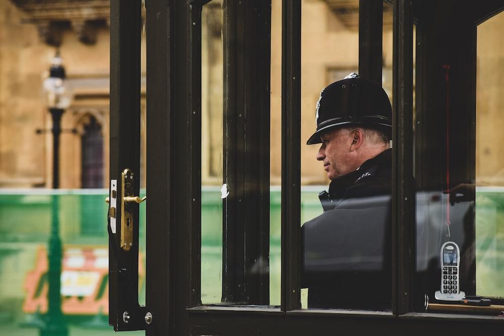 man inside black framed clear glass cubicle on street