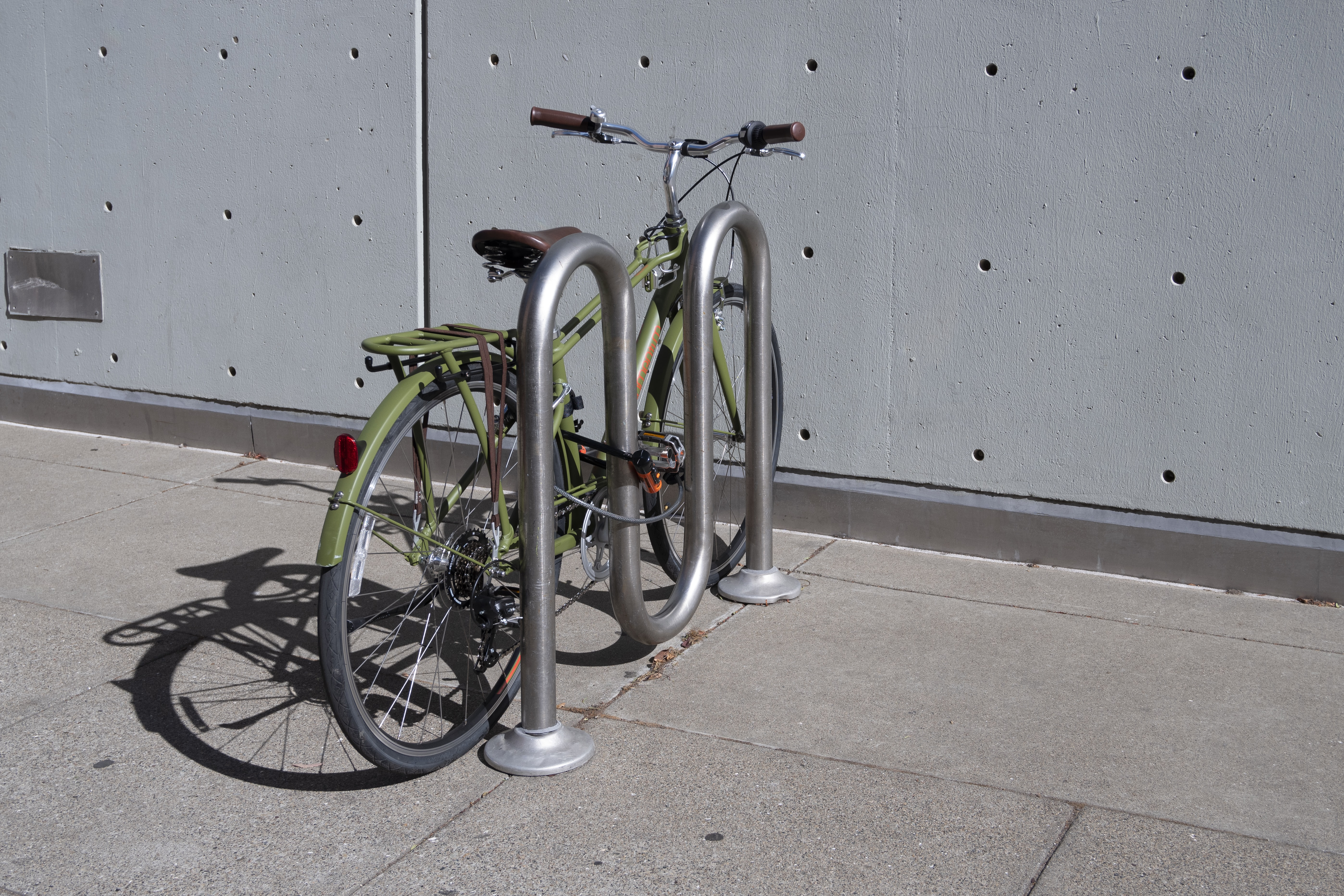 green city bicycle parked near wall during daytime