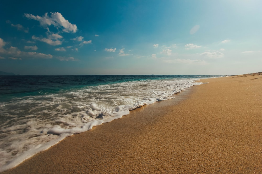 nature photography of shore and brown sand during daytime