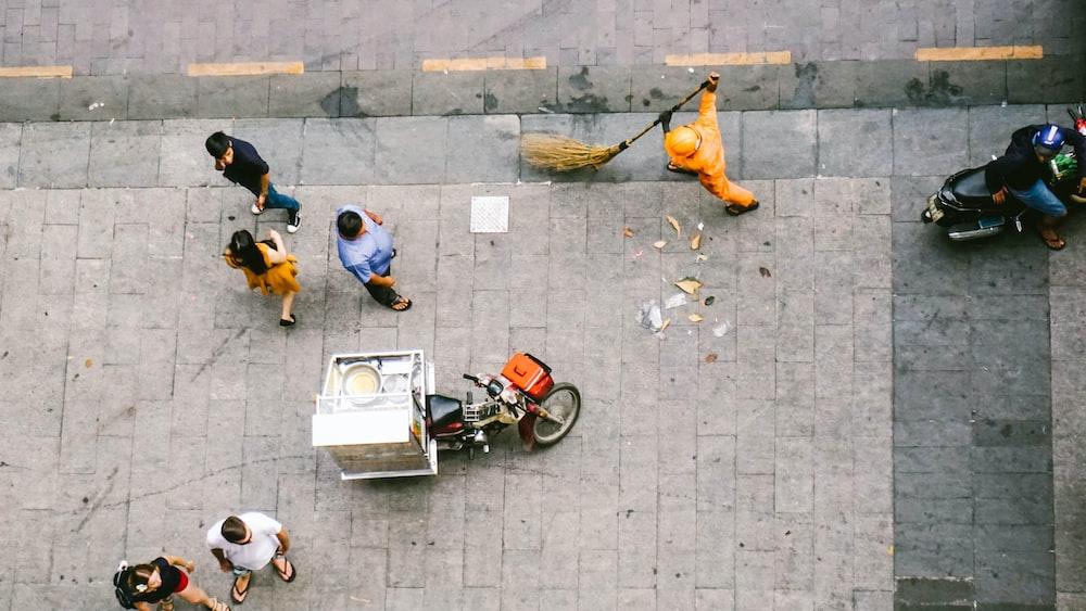 people walking near man sweeping on road during daytime