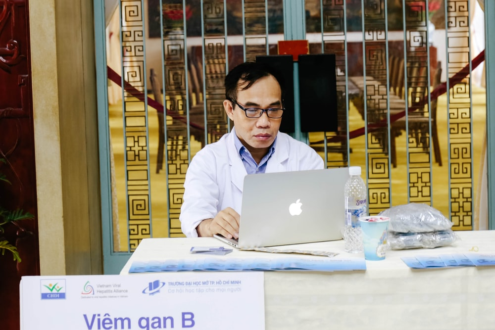 man using silver MacBook near blue metal gate