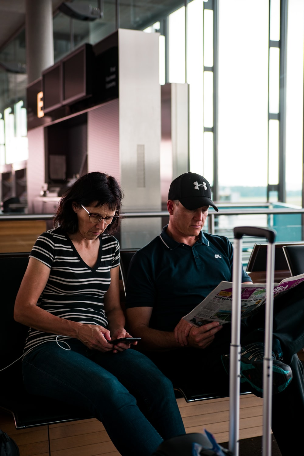 woman fiddling on smartphone beside man with cap reading newspaper