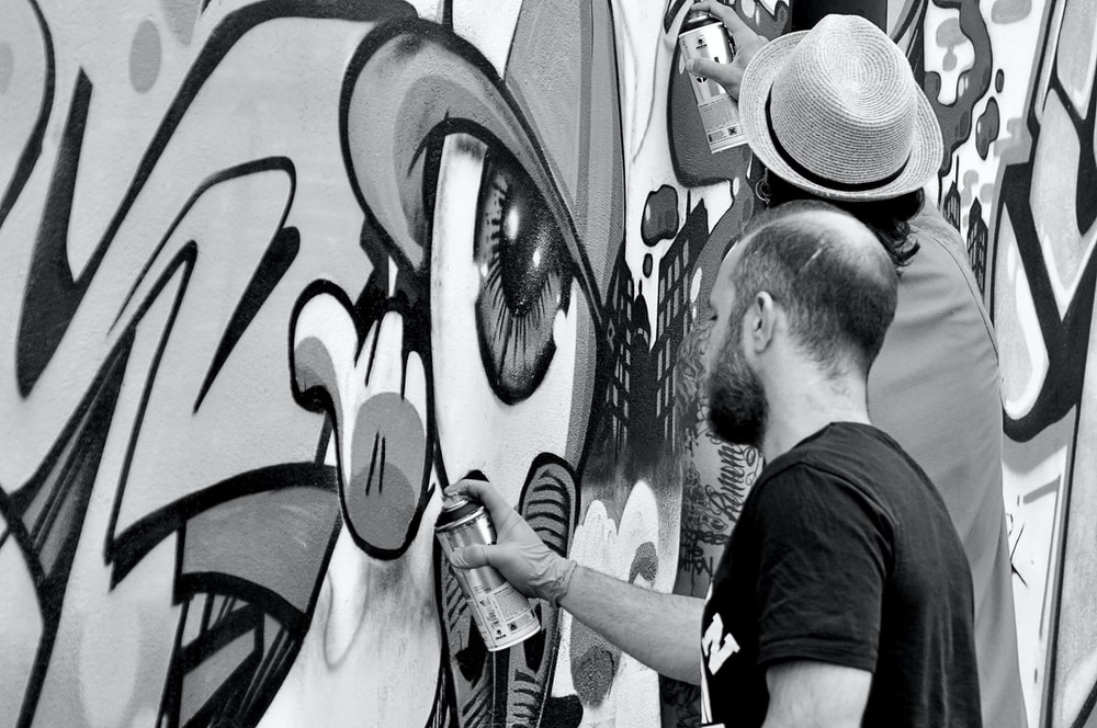 grayscale photography of two artists spraying graffiti wall