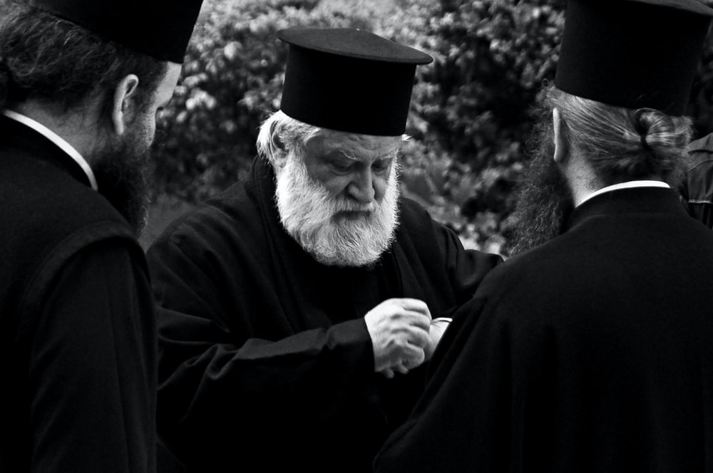 grayscale photography of three men wearing black robes and hats