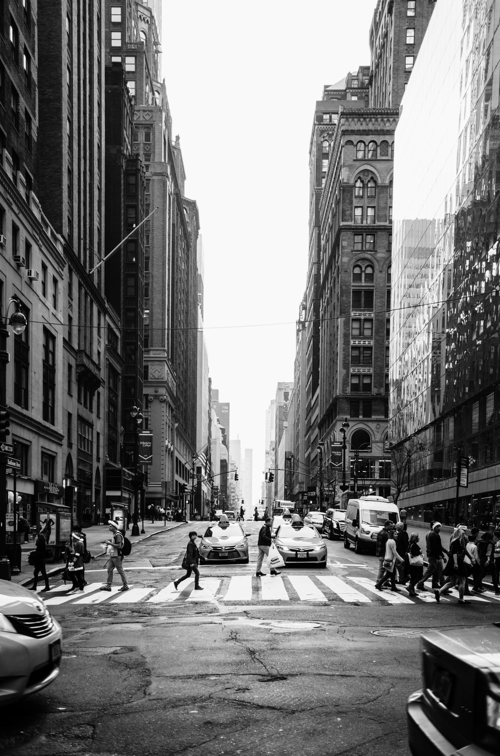 grayscale photo of people crossing the road
