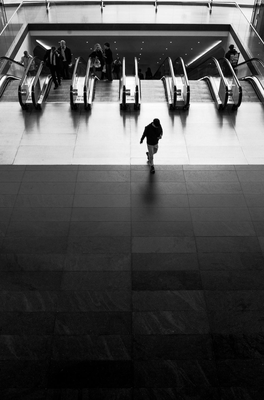 grayscale photography of man walking near escalator
