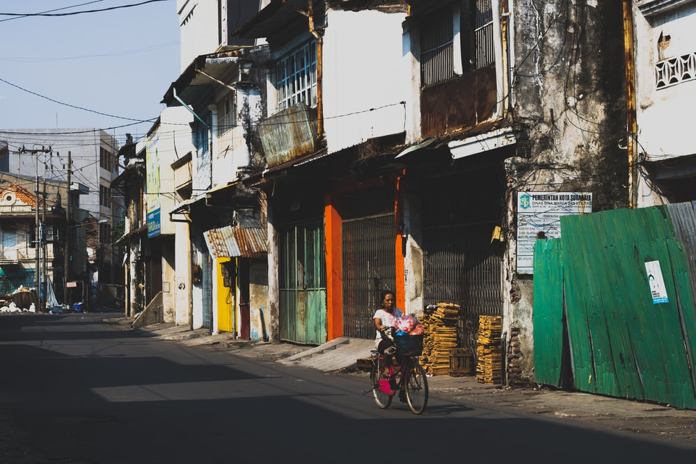 woman riding bicycle near houses