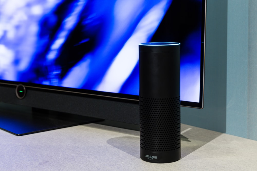 black amazon echo smart speaker near turned-on flat screen TV