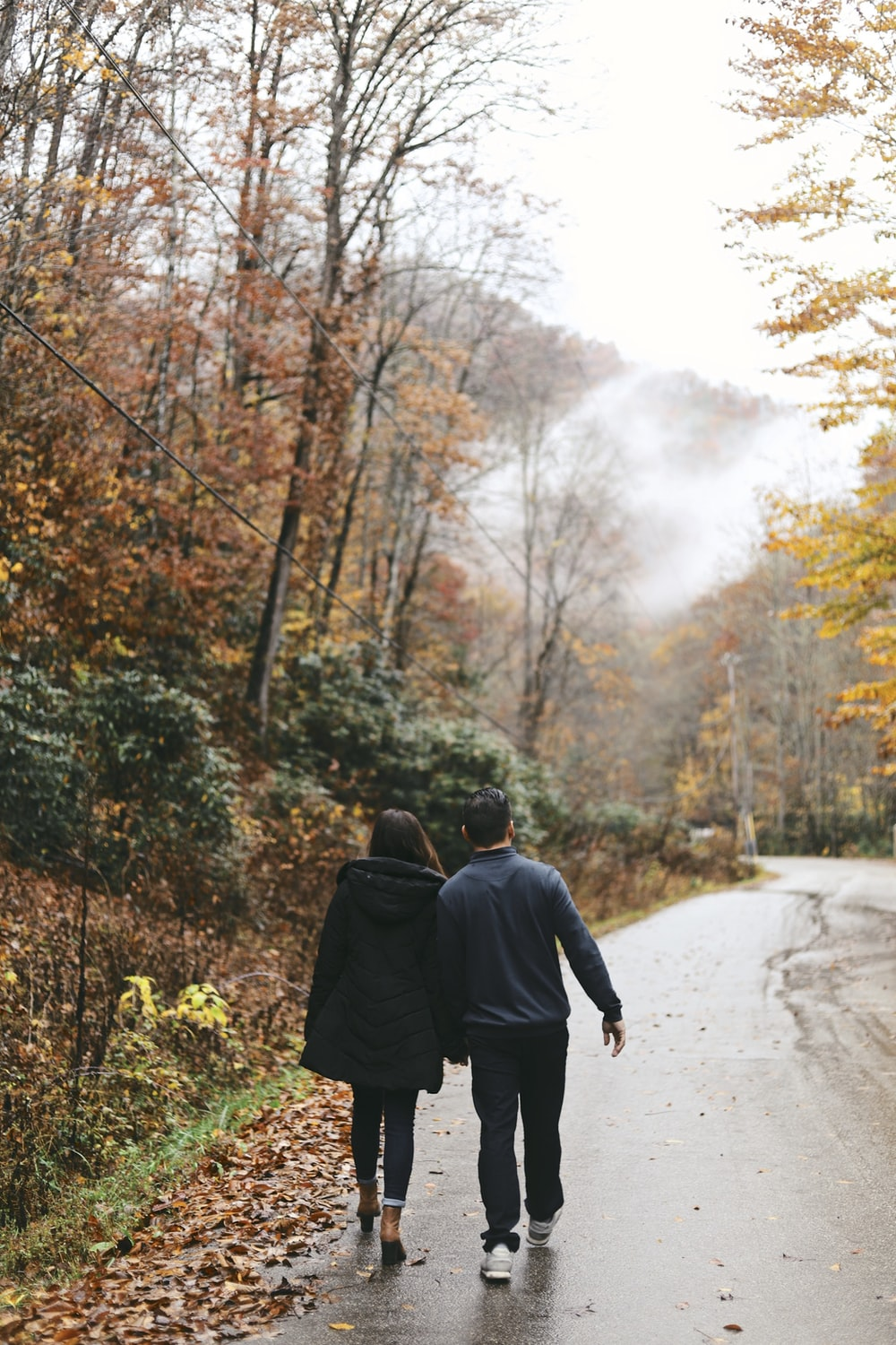 couple walking at the road between trees